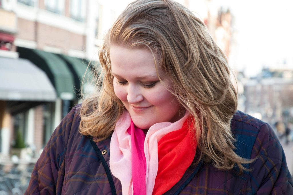 Photo of Sara looking down while wearing a winter coat and scarf