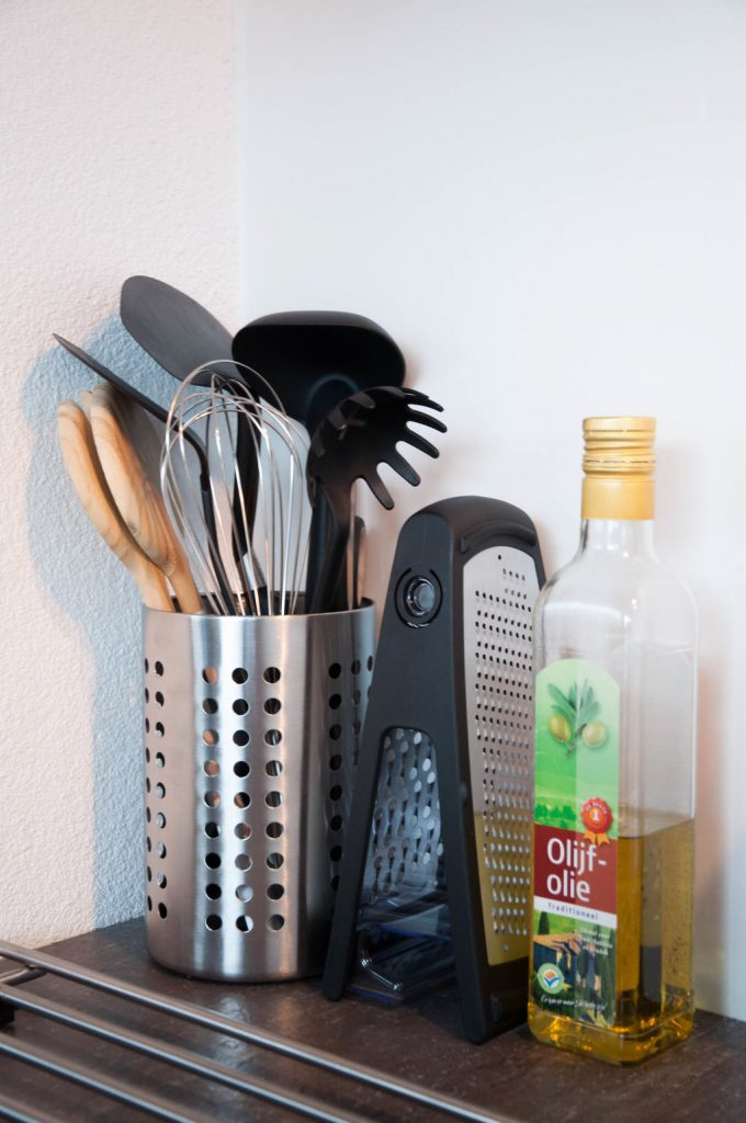 A picture of kitchen utensils, a cheese grater, and a bottle of olive oil next to a stove. First Kitchen Essentials for Your New Apartment