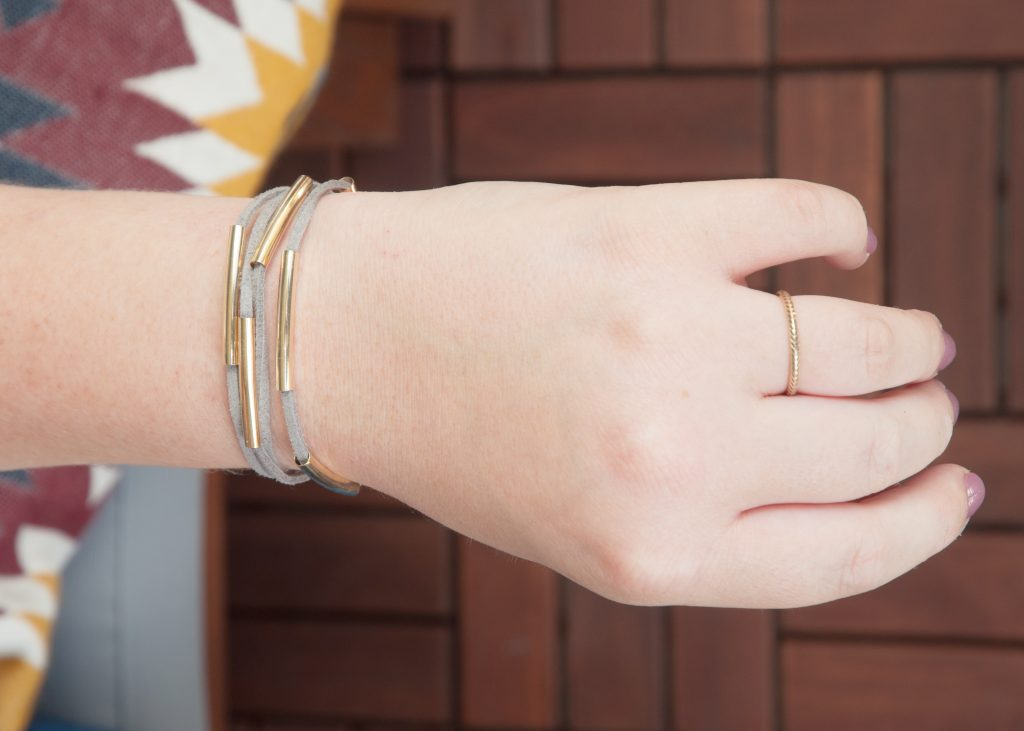 3 Easy DIY Bracelets You'll Actually Want to Wear. Image Description: A wrist featuring a gray wrap bracelet with gold beads, and wearing a gold ring.