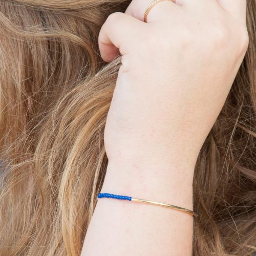 3 Easy DIY Bracelets You'll Actually Want to Wear. Image Descriotion: A hand modeling a blue and gold bracelet.