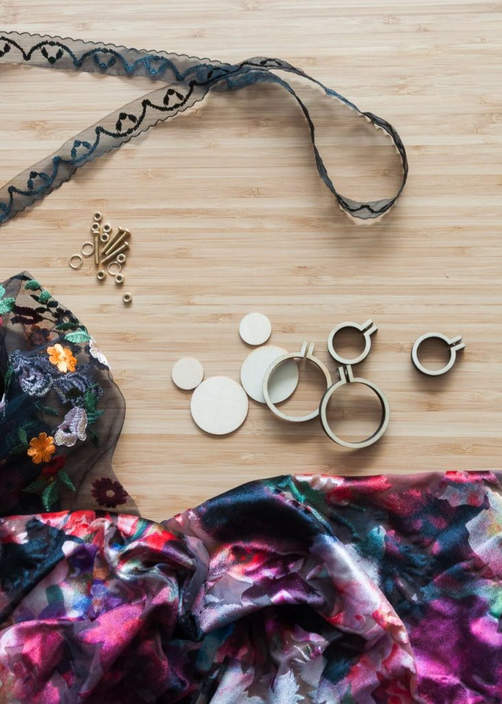 How to Make No-Sew Mini Embroidery Hoop Necklaces. Image Description: fabric and mini embroidery hoops on a desk.