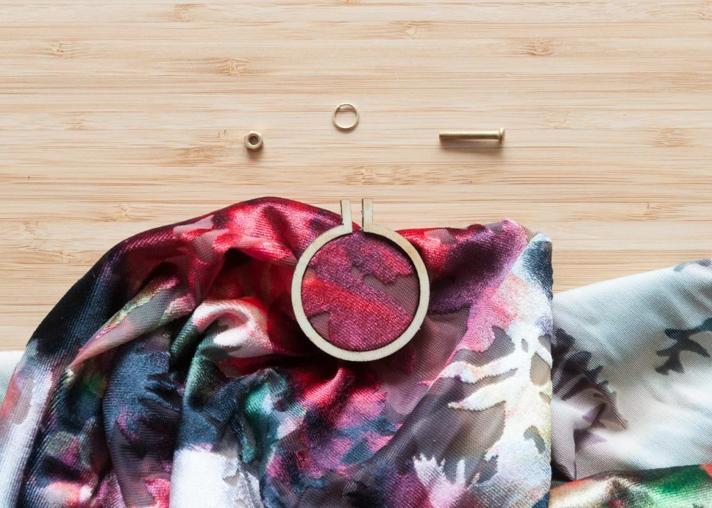 How to Make No-Sew Mini Embroidery Hoop Necklaces. Pictured: A mini embroidery hoop on red velvet fabric.