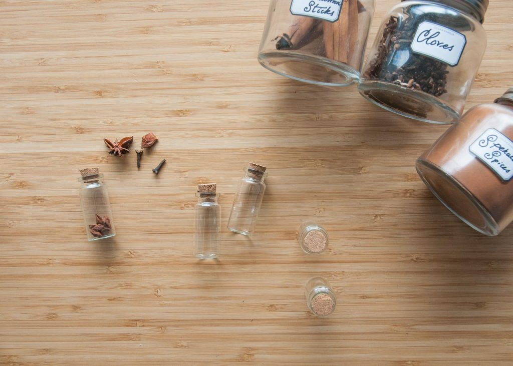 How to Make Apothecary Spice Jar Necklaces for Fall. An array of jars and spices on a table.