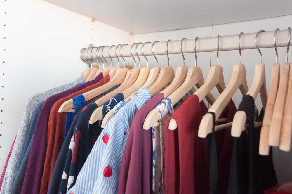 A picture of several clothing items hanging in a closet