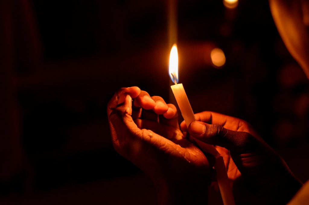 Two hands holding a candle. In memory of Rachel Held Evans