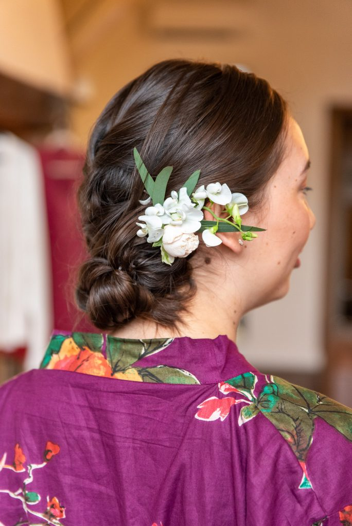 One bridesmaid's hairstyle, a braided bun with white flowers behind her ear.